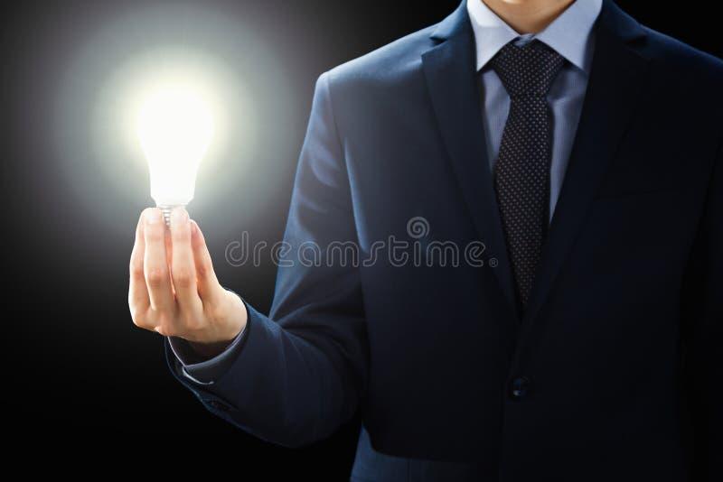 O conceito, mãos da terra arrendada do homem de negócios iluminou o sinal da ampola fotografia de stock