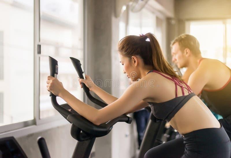 O conceito saudável do estilo de vida, exercício da mulher do jovem adolescente com centro interno fazendo de ciclagem do cardi fotografia de stock