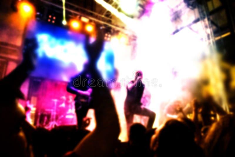 O concerto de rocha borrou a opinião do fundo da audiência, dos músicos da rocha com guitarra e do vocalista fotografia de stock