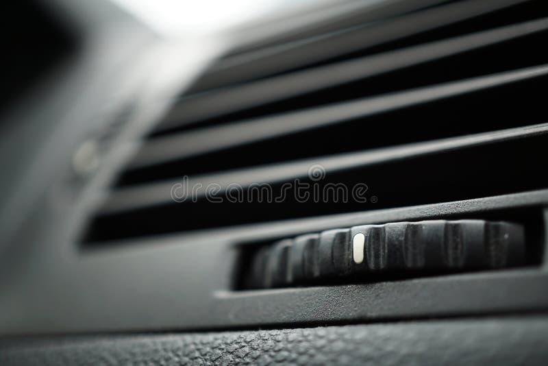 O condicionamento de ar automotivo moderno do carro (respiradouro da ventilação do carro) com inclinação arredondou o controle ro imagens de stock