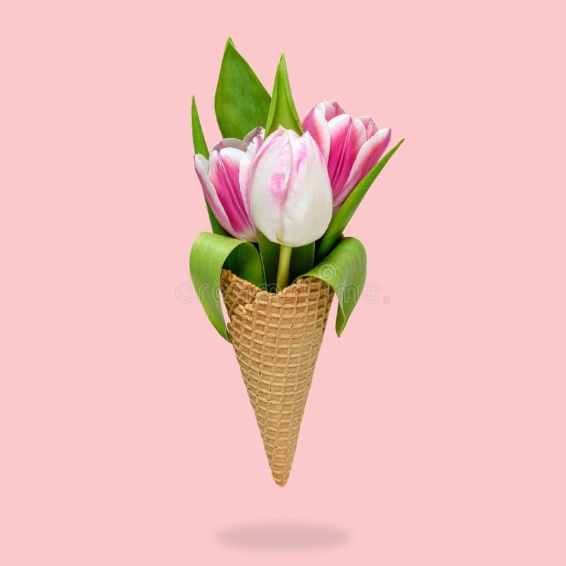 O cone de gelado com tulipa floresce no fundo cor-de-rosa fotografia de stock royalty free