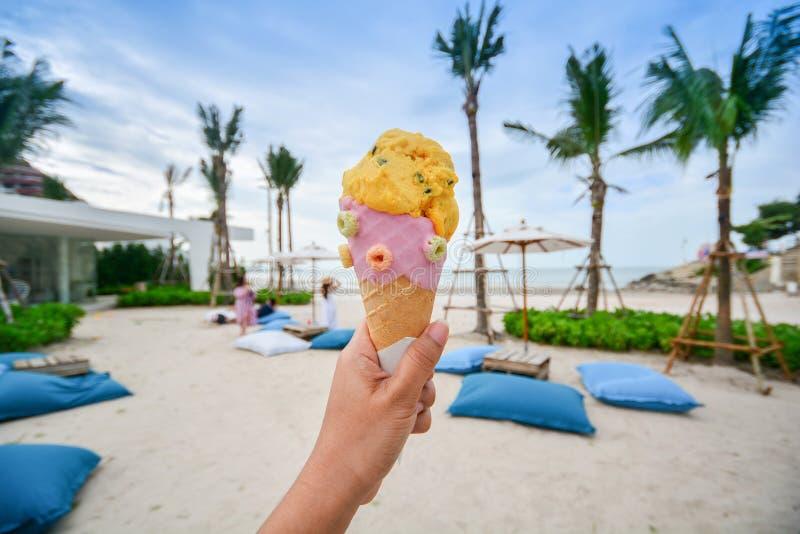 O cone de gelado guardou na praia com céu agradável, verão imagem de stock