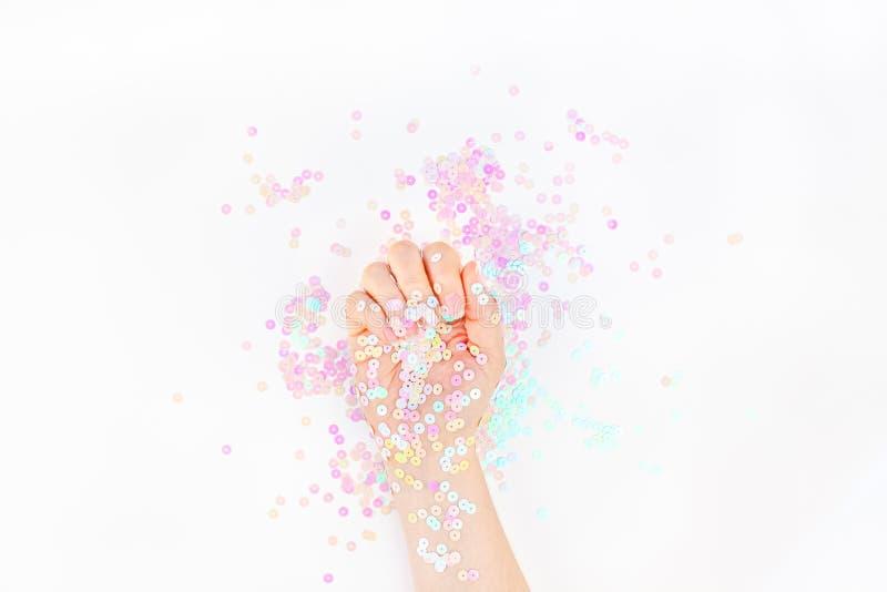 O confete pastel da p?rola sparkles com m?o da mulher imagem de stock royalty free