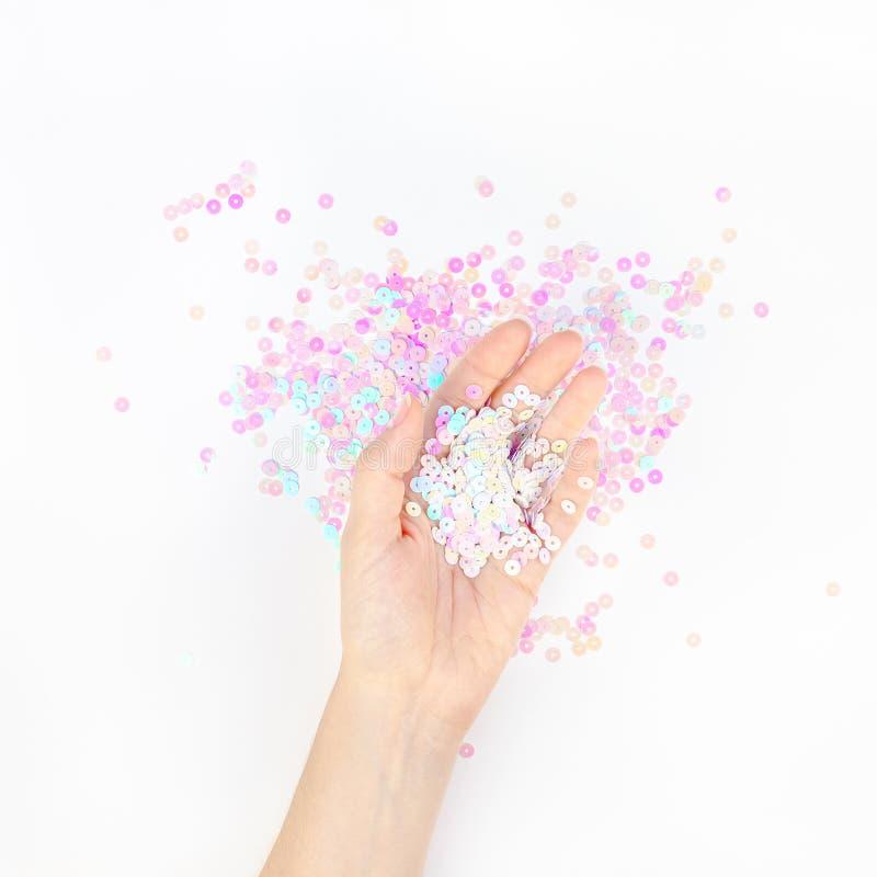 O confete pastel da p?rola sparkles com m?o da mulher imagens de stock