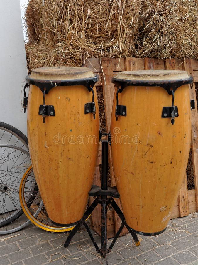 O Conga rufa com fundo a de madeira e de bicicleta da roda do feno ou da palha, imagem de stock