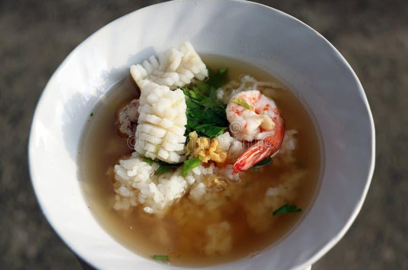 O congee do arroz misturado com o camarão, o calamar e a carne de porco, decora com coentro e preservado do aipo fotografia de stock
