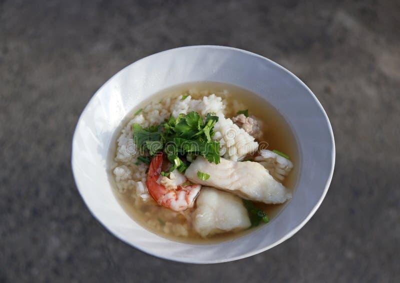 O congee do arroz misturou com o camarão, peixe, calamar e a carne de porco, decora com coentro imagem de stock royalty free