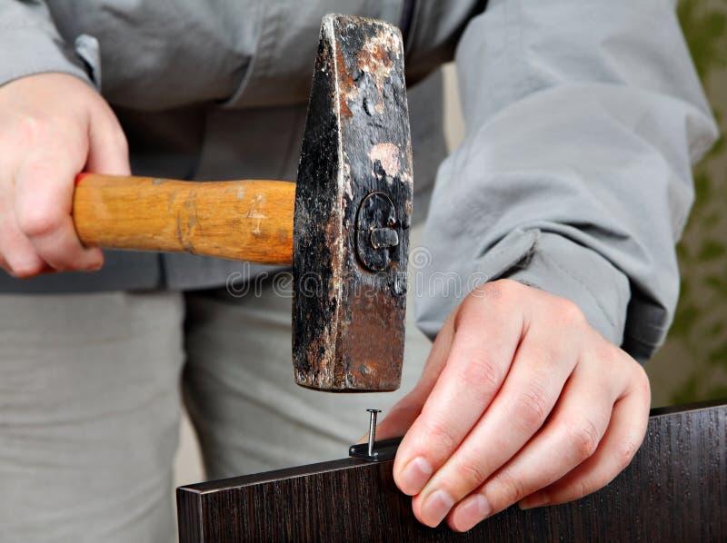 O conjunto da mobília, trabalhos, martelo do close up bate o prego imagem de stock royalty free