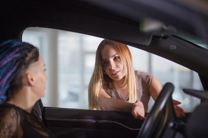 O conselheiro dá a consulta à mulher Azul-de cabelo na sala de exposições do carro fotografia de stock