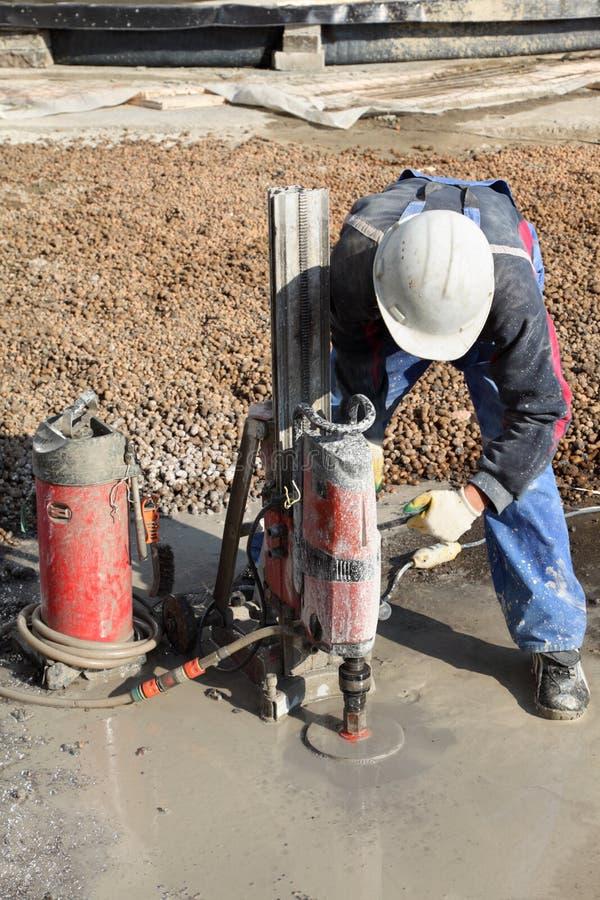 O construtor aperta os parafusos na fundação concreta úmida. imagem de stock royalty free