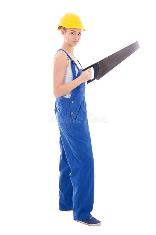 O construtor da jovem mulher em combinações azuis com serra manual isolou o imagens de stock royalty free