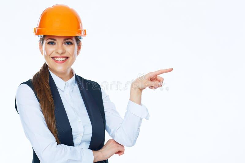 O construtor da mulher no capacete aponta o dedo no espaço da cópia fotografia de stock