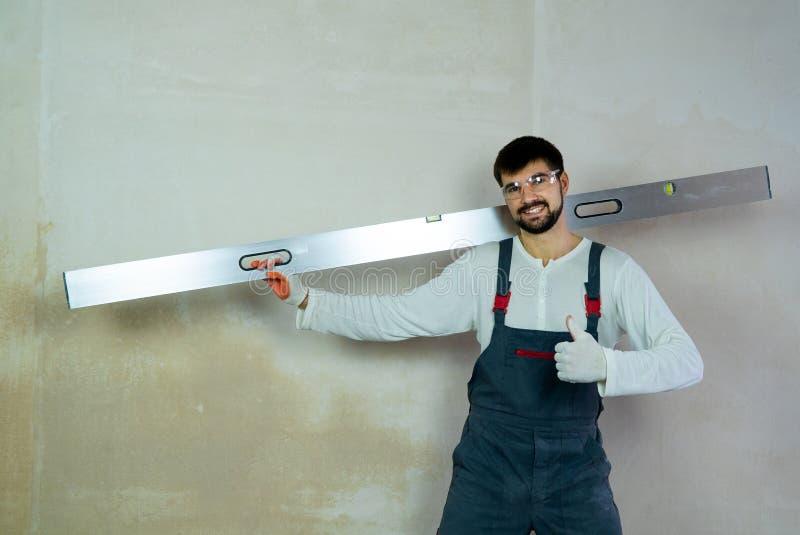 O construtor de sorriso com mostras da régua da construção manuseia acima no espaço livre interior imagens de stock royalty free