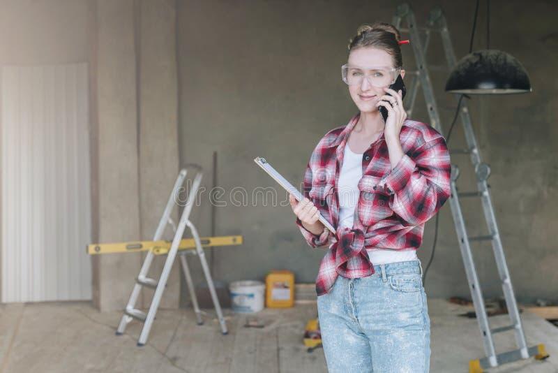 O construtor de sorriso novo da mulher de negócios, coordenador, arquiteto, desenhista em vidros da construção está estando na of foto de stock