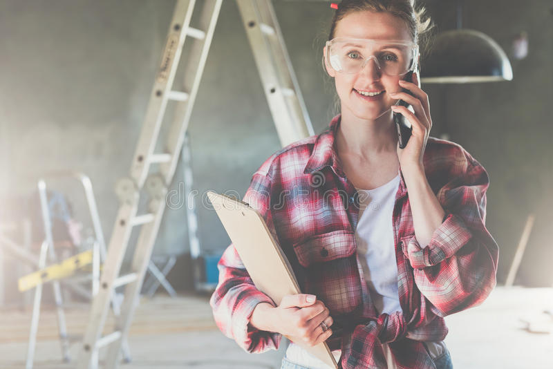 O construtor de sorriso novo da mulher de negócios, coordenador, arquiteto, desenhista vestiu-se em vidros da camisa e da constru fotos de stock royalty free