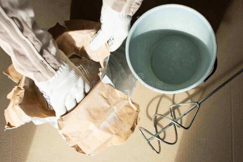 O construtor do homem prepara uma mistura para a massa de vidraceiro foto de stock royalty free