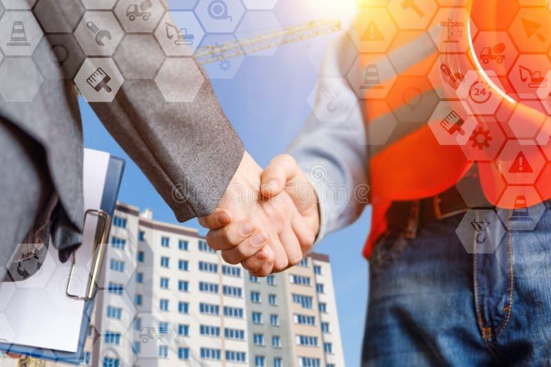 O construtor e a mulher de negócios selaram o negócio com um aperto de mão imagem de stock