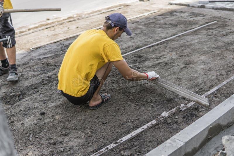O construtor em sua camisa gloved e amarela alaranjada prepara a superfície antes de colocar as pedras de pavimentação com a régu imagens de stock royalty free