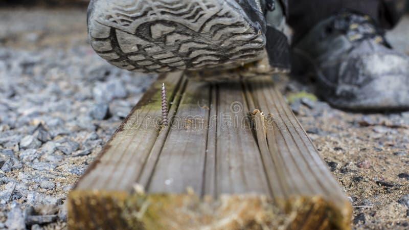 O construtor está inscrevendo um parafuso afiado em Finlandia No pé tem uma sapata de segurança fotos de stock