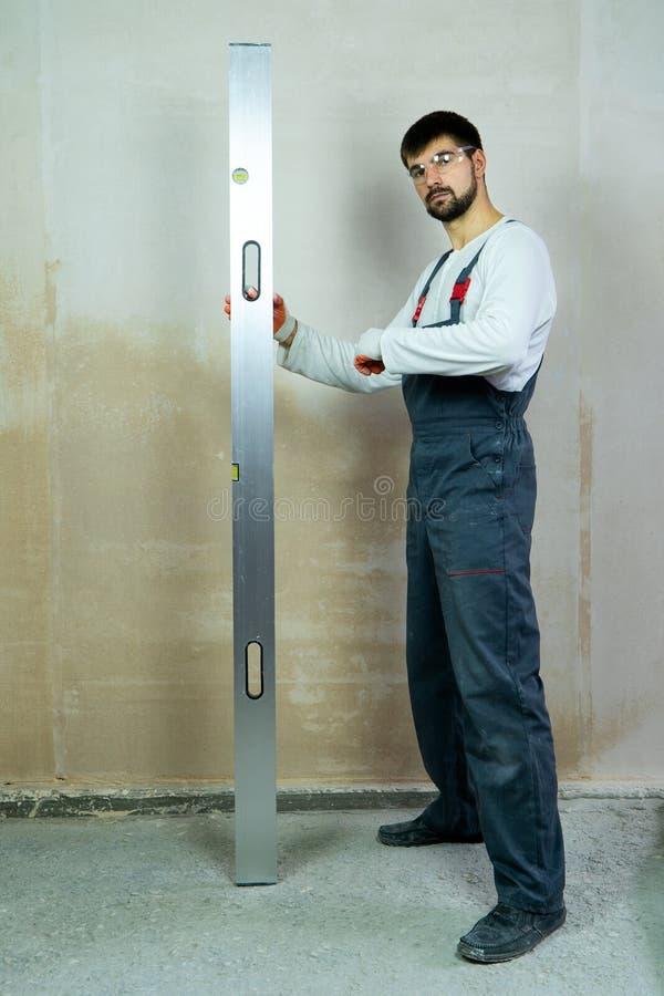 O construtor farpado novo está perto da parede vazia com régua da construção fotografia de stock royalty free