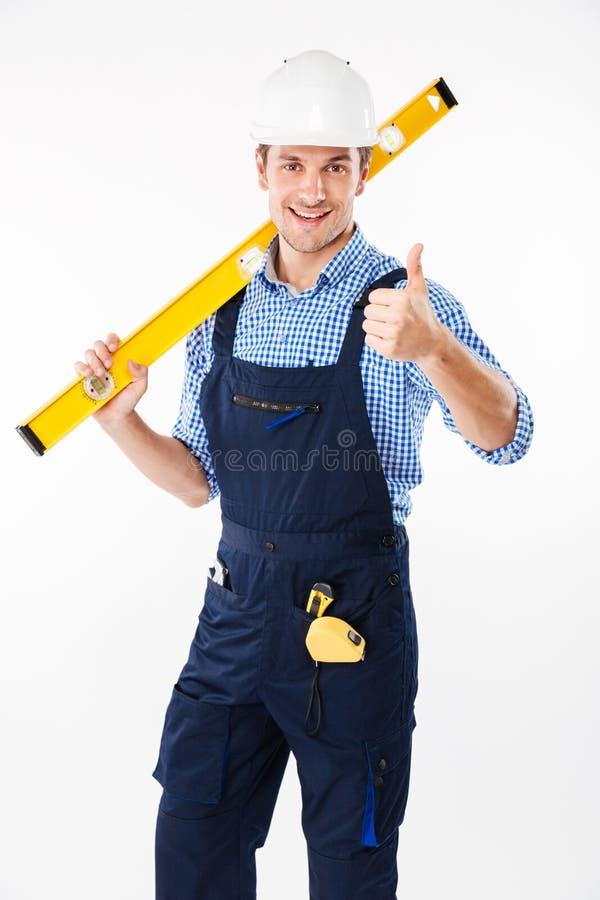 O construtor masculino de sorriso que está e que mostra manuseia acima do gesto fotografia de stock royalty free