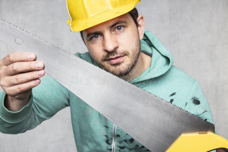 O construtor mostra uma nova serra para cortar, fechar foto de stock