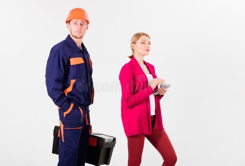 O construtor no capacete esperar quando mulher com cara ocupada fotografia de stock