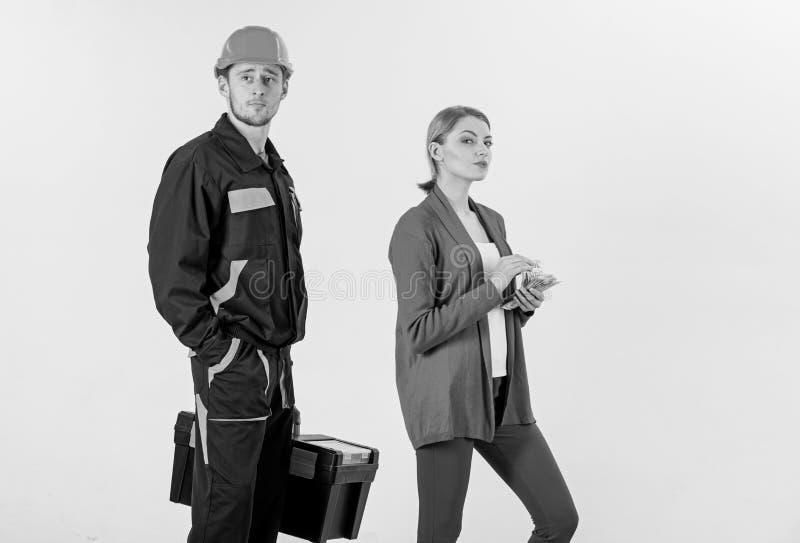 O construtor no capacete esperar quando mulher com cara ocupada imagem de stock royalty free