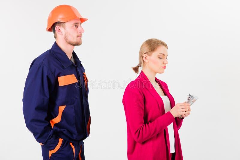 O construtor olha a mulher com a cara ocupada que conta o dinheiro, fotografia de stock royalty free