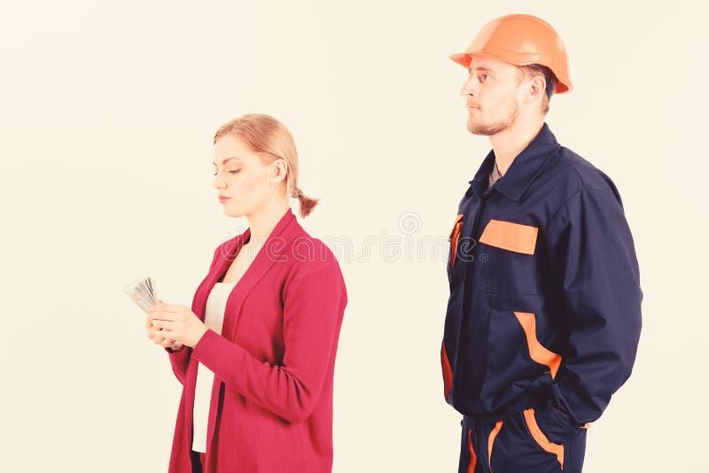 O construtor olha a mulher com a cara ocupada que conta o dinheiro, imagem de stock royalty free