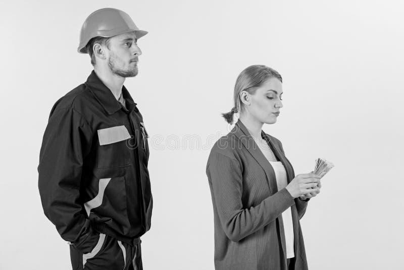 O construtor olha a mulher com a cara ocupada que conta o dinheiro, foto de stock