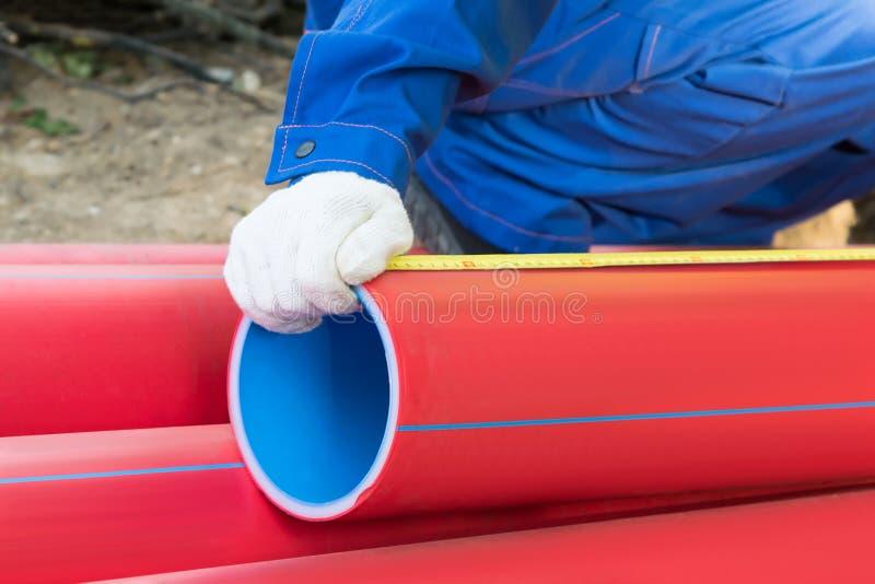 O construtor pega uma parte de tubulação vermelha, fim do fundo foto de stock royalty free
