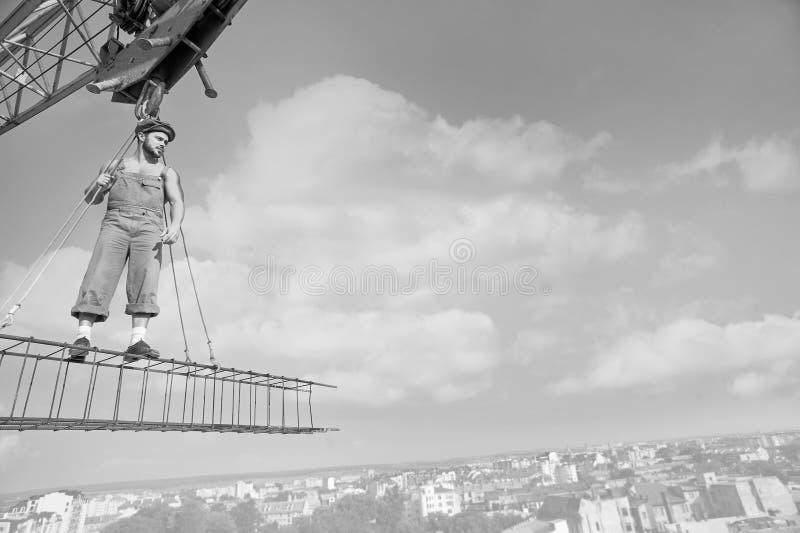 O construtor profissional vestiu-se no equipamento do vintage que levanta em uma cruz foto de stock