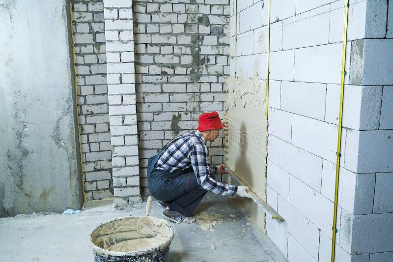 O construtor que senta-se no seu hunkers o emplastro na parede do bloco imagens de stock