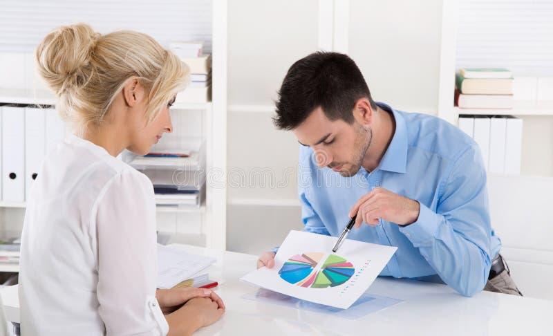 O consultante explica o sucesso financeiro a seu cliente com um grap fotografia de stock
