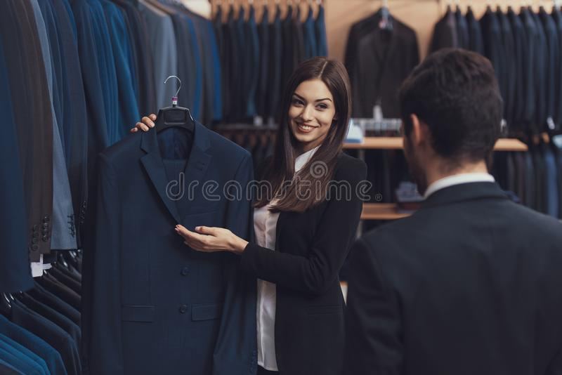 O consultante fêmea bonito da loja do menswear ajuda a escolher o revestimento para o homem novo no terno fotos de stock