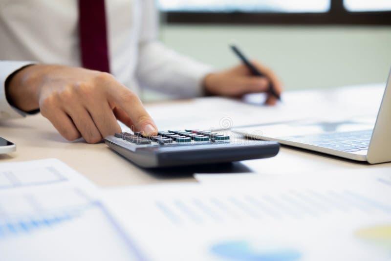 O contador ou o banqueiro masculino calculam a conta do dinheiro imagens de stock