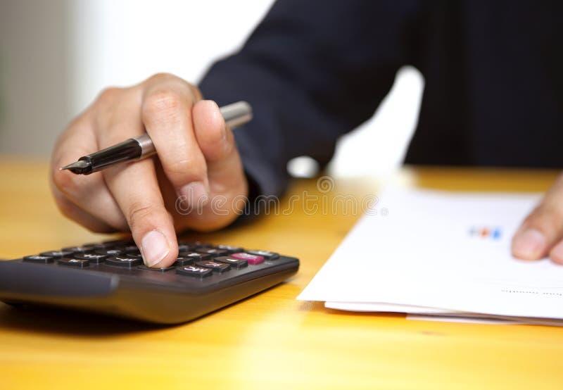 O contador ou o homem de negócios estão calculando impostos com calculadora imagens de stock royalty free