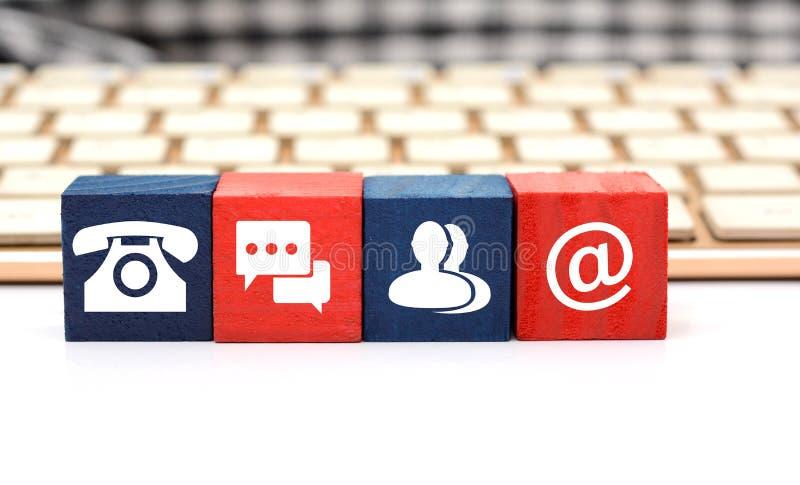 O contato significa ícones em dados de madeira com o teclado no fundo imagem de stock