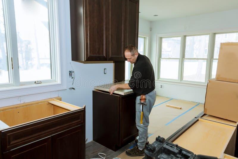 O contratante que instala uma parte superior contrária estratificada durante uma cozinha remodela imagem de stock