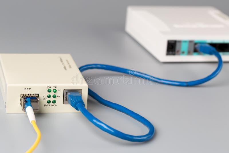 o conversor ótico dos meios 1Gbps com módulo de SFP conectou ao roteador de SOHO da porta ethernet imagens de stock royalty free