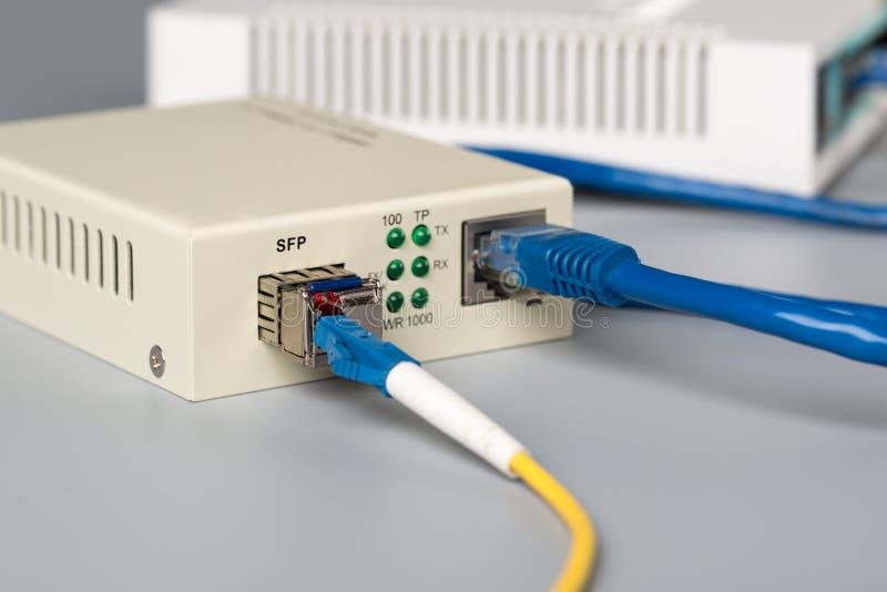 o conversor ótico dos meios 1Gbps com módulo de SFP conectou ao roteador de SOHO da porta ethernet foto de stock royalty free