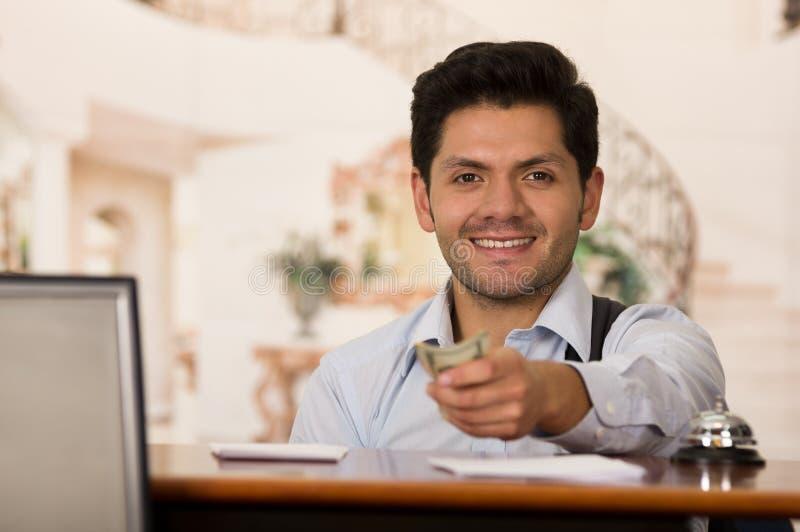 O convidado de sorriso paga a conta do hotel foto de stock