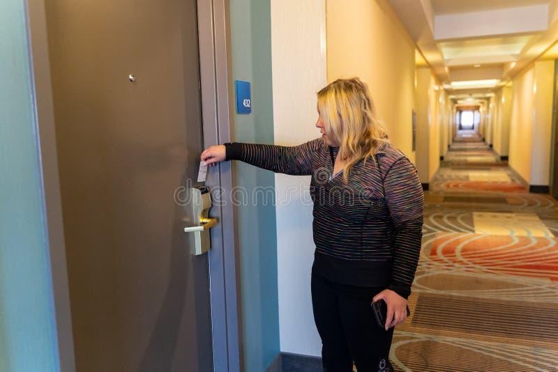 O convidado do hotel da mulher destrava sua porta da sala com seu cartão chave do corredor imagem de stock royalty free
