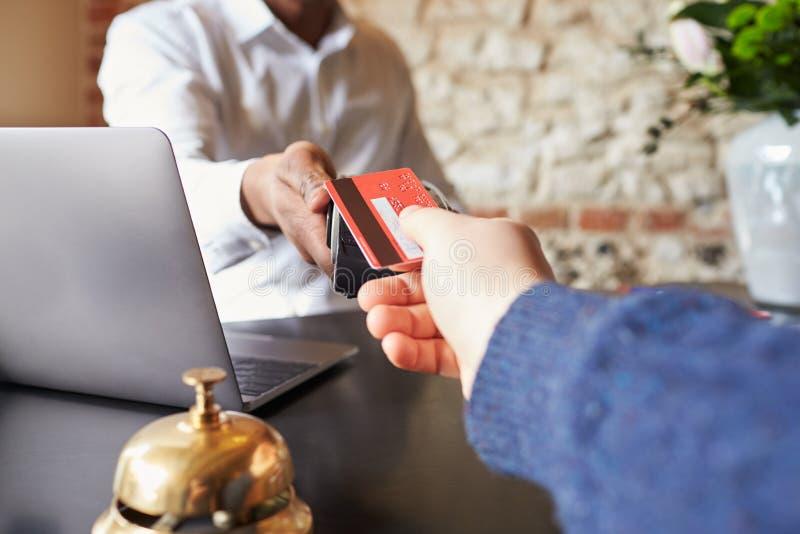 O convidado faz o pagamento do cartão na mesa de registro do hotel, detalhe foto de stock