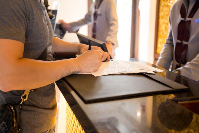 O convidado masculino verifica dentro no hotle que assina um formulário na recepção imagens de stock royalty free