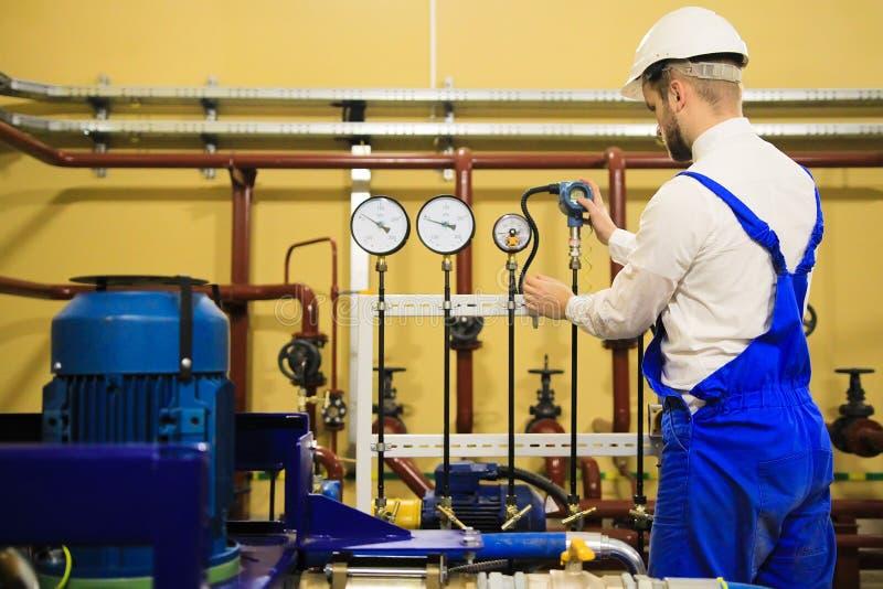 O coordenador ajusta sensores da pressão na planta de refinaria industrial fotos de stock royalty free
