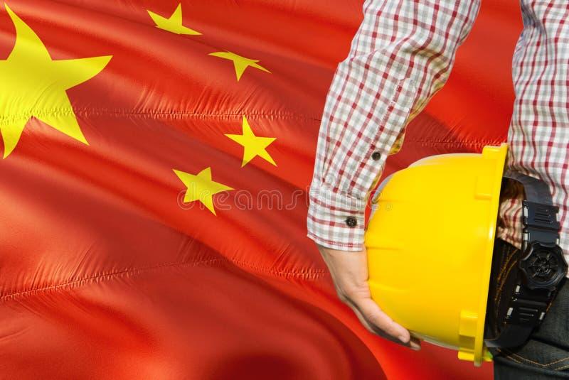 O coordenador chinês está guardando o capacete de segurança amarelo com ondulação do fundo da bandeira de China Conceito da const fotos de stock