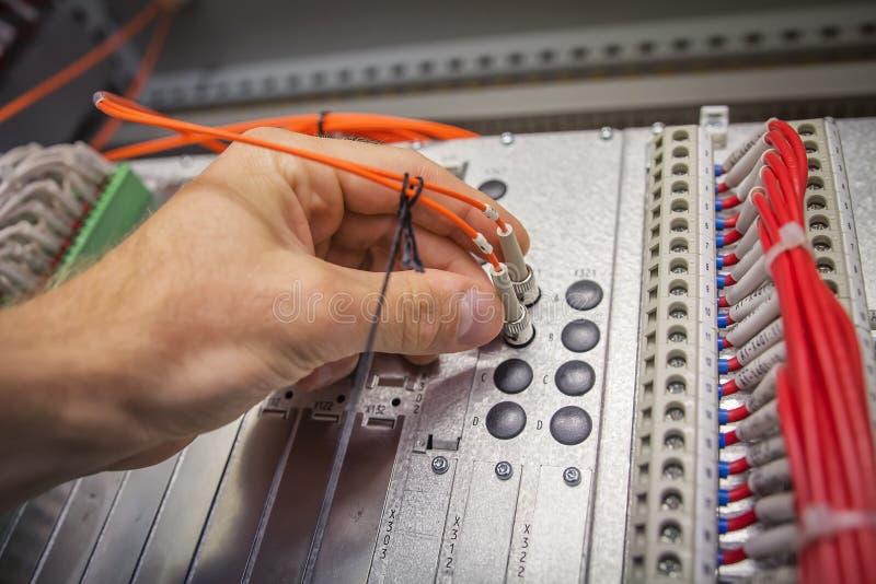 O coordenador conecta o cabo de remendo da fibra ótica a uma comunicação industrial do dispositivo no close-up do centro de dados fotografia de stock