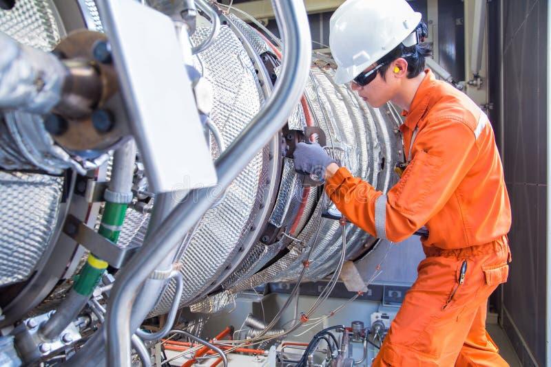 O coordenador da turbina que veste o equipamento de proteção pessoal inspeciona o motor de turbina do gás na plataforma a pouca d foto de stock royalty free
